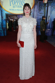 Emily Mortimer gave her dress a splash of color with a red velvet envelope clutch.