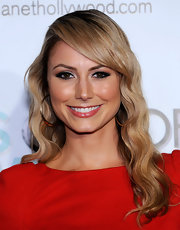 Stacy Keibler showed off her blonde tresses while posing for the cameras. Her red dress is a great color for the Actress and gold hoops were the perfect accent.