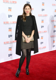 Amanda Peet attended the premiere of 'American Crime Story: The People v. O.J. Simpson' looking preppy in a black wool coat layered over a crewneck sweater and a plaid mini skirt.