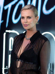 Charlize Theron exposed her black Dior bra underneath a sheer blouse at the premiere of 'Atomic Blonde.'