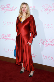 Courtney Love looked dramatic in a red Roksanda satin dress with draped sleeves and a high-low hem at the premiere of 'The Beguiled.'