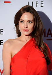 Angelina Jolie styled her chestnut brown hair in a side parted layered hairstyle.