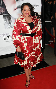 Chandra dons a bold print wrap dress with sparkling black accessories and red satin evening sandals.