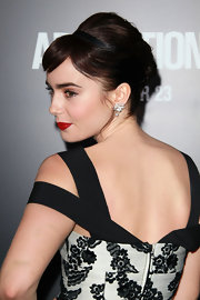 To duplicate Lily Collins' look, begin by sectioning out bangs, then backcomb the hair, especially through the crown. Next, throw on a slim headband and smooth tresses back to the nape of the neck. Twist hair vertically to create a low French twist and secure by inserting bobby pins horizontally into the twist, next to the scalp. To finish the look, sweep bangs across the forehead and mist with hairspray.