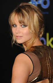 Jennifer Lawrence attended the premiere of 'The Hunger Games' wearing her hair in a romantic updo with gold braid accent and wispy bangs with face framing-tendrils.