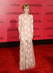 Bella Thorne looked subtly sexy in a sheer nude Blumarine gown with white floral embroidery during the 'Catching Fire' LA premiere.