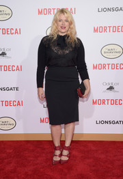 For a bit of edge and color, Amanda de Cadenet wore strappy red ankle-cuff pumps with her black outfit.
