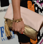 Arden Myrin sported an oversized gold and pink fold-over clutch.