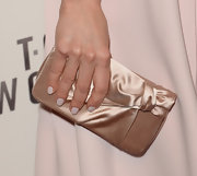 Olga Kurylenko topped off her purely feminine look with this champagne-colored satin clutch.