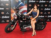 Debby Ryan posed on a motorcycle at 'The Avengers' premiere wearing a pair of strappy denim blue and tan platform sandals.