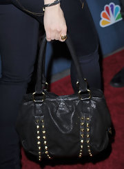 Mena Suvari toughened up her red carpet look with a black leather purse embellished with gold studs.