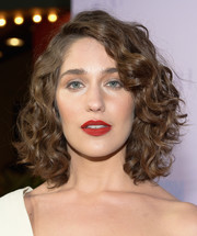 For her beauty look, Lola Kirke teamed matte red lipstick with neutral eyeshadow.