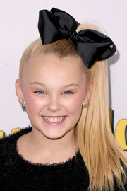 JoJo Siwa added a bit of sparkle with a pair of gold bow earrings.