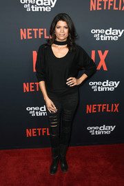 Andrea Navedo attended the premiere of 'One Day at a Time' season 2 wearing a black scoopneck sweater with choker detail.