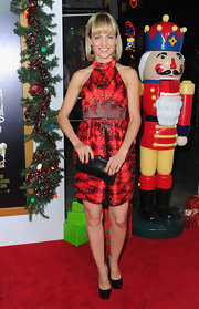 Mena Suvari complemented her bold fiery print frock with a sleek black frame clutch at the premiere of 'A Very Harold & Kumar 3D Christmas.'