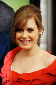 Amy Adams pinned updo shows off the actresses decadent  earrings and elaborate neckline of her bright red dress.