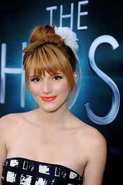Bella Thorne's hair was oh-so pretty with this messy top knot and adorable white flower as a hair accessory.