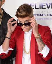 Justin Bieber glitzed up his outfit with a layered chainlink necklace for the premiere of 'Justin Bieber's Believe.'