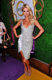 Paris Hilton kept the focus on her dazzling silver satin embroidered frock with classic taupe patent platforms.