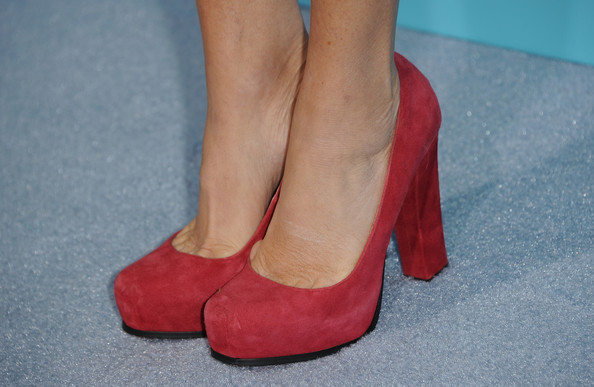 Marcia Gay Harden matched her pop of red up top with red suede platform pumps.