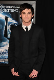 Logan wears a unique black suit with varying textures over a v-neck sweater and tie for the movie premiere.