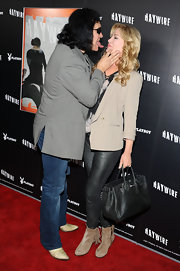 Shannon Tweed braced herself for a red carpet kiss carrying a luxe black woven tote.