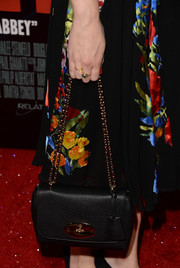 Cara Theobold complemented her floral frock with a classic black chain-strap bag when she attended the premiere of 'Romeo and Juliet.'