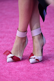 Soft pink bow tie pumps by Atelier Versace added a pop of whimsy to Mila's look.