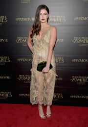 Millie Brady paired her dress with an elegant emerald velvet clutch.