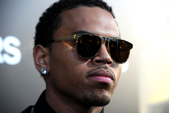 Chris Brown paired his gold rimmed sunglasses with large diamond stud earrings.