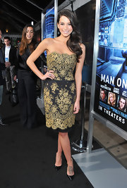 Genesis accessorized her black and gold cocktail dress with black d'orsay pumps.