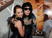 Trace Cyrus wears his retro black wayfarer sunglasses - and poses with famous sister Miley.