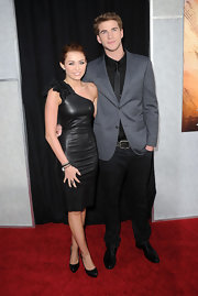 Miley made her coupled-up red carpet debut wearing a fitted black leather dress with a pair of black platform pumps. This was a very mature look for the young starlet.