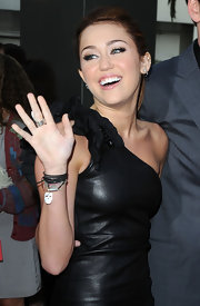 "Miley loves her mix and match accessories. The actress completed her leather look with a jumble of pieces including the ""Mother of Pearl Charm Bracelet""."