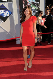 Brianna Evigan paired her nude pumps with a one-shoulder orange red dress.