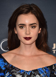 Lily Collins opted for a simple loose hairstyle with an off-center part when she attended the premiere of 'Jeremy Scott: The People's Designer.'