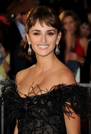 Penelope Cruz accented her chignon with elegant diamond earrings.