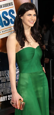 Alexandra Daddario added elegance to her emerald gown with a golden hard case Kotur clutch.