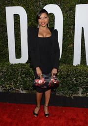 Taraji P. Henson complemented her outfit with an elegant floral satin clutch.