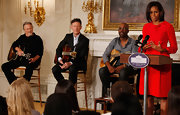 Michelle Obama chose a conservative yet stylish bow-adorned red dress for a music program at the White House.