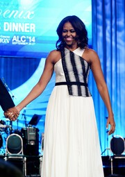 Michelle Obama stuns in a graphic black and white belted halter dress.