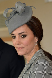 Kate Middleton attended a ceremony at the Royal Garden Hotel wearing a beribboned gray hat by Jane Taylor.