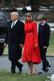 Melania Trump paired her coat with tan suede pumps by Jimmy Choo.