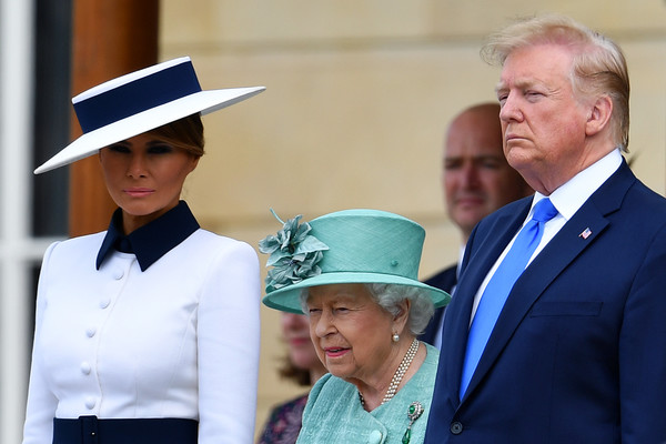 Melania Trump coordinated her dress with a white and blue wide-brimmed hat by Herve Pierre for her visit to Buckingham Palace.