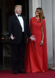 Melania Trump was a vision in a red cape-sleeve gown by Givenchy while attending a dinner during the State Visit to England.