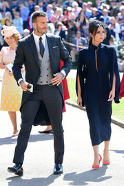Victoria Beckham opted for a simple navy midi dress with split sleeves when she attended the wedding of Prince Harry and Meghan Markle.
