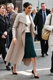 Meghan Markle layered a sand-colored wool coat by Mackage over a white top and a green skirt for her visit to Belfast.