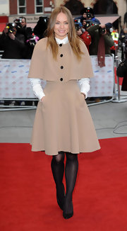 Laura Haddock chose a nude evening coat with a flared skirt for her classically cool red carpet look.