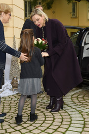Charlene Wittstock layered an aubergine cashmere coat over a matching dress, both by Loro Piana, for the Christmas gifts distribution at La Croix Rouge in Monte Carlo.