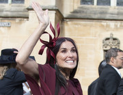 Demi Moore paired her burgundy dress with a matching ribbon fascinator by Stephen Jones for Princess Eugenie's wedding.